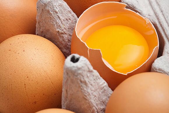 Carton tray of brown eggs with visible yellow yolk