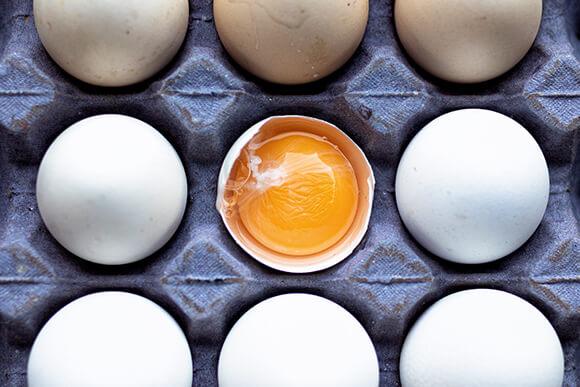 A carton of white eggs, one yellow yolk